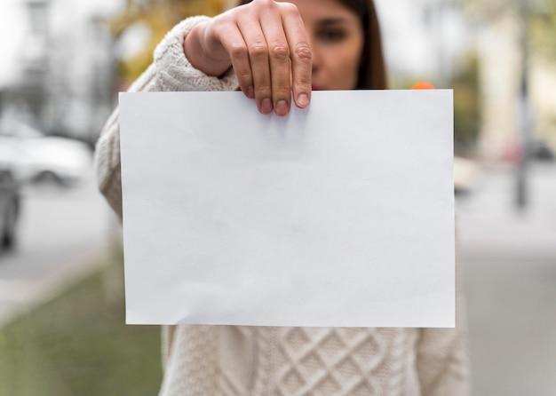 Porträt einer frau, die ein leeres papier hält