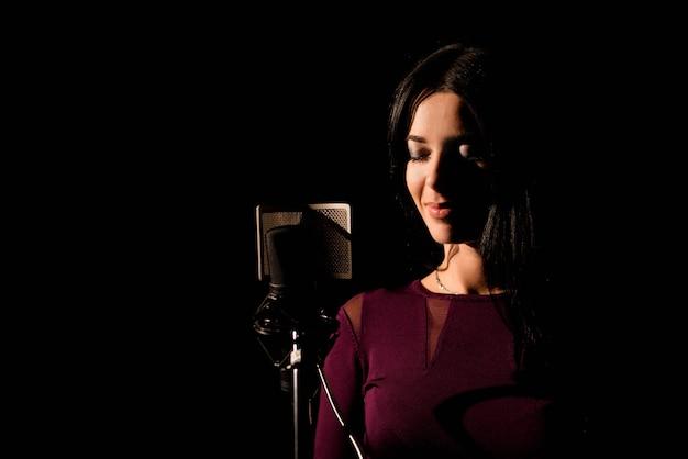 Porträt einer frau, die ein lied in einem professionellen studio aufzeichnet