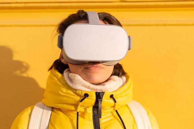 Porträt einer frau, die eine brille der virtuellen realität auf der straße gegen eine gelbe wand in hellem sonnenlicht im winter in warmer kleidung trägt