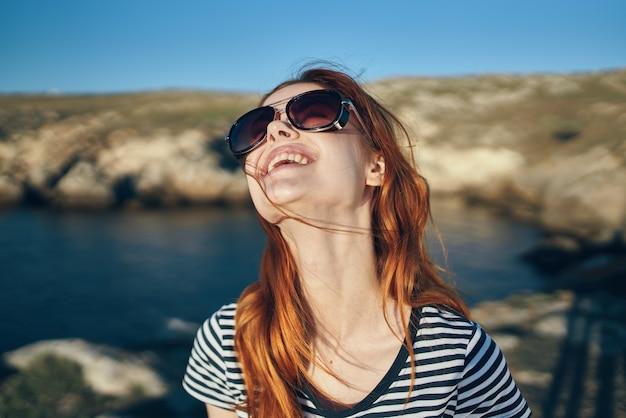 Porträt einer frau, die eine brille im freien im gebirgstourismus trägt, reist klares wasser seefluss