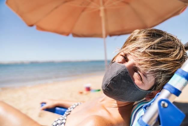 Porträt einer frau, die eine gesichtsmaske in den sommerferien trägt, die in der sonne auf einem strandkorb direkt neben einem orangefarbenen regenschirm mitten in einer coronavirus-pandemie liegt