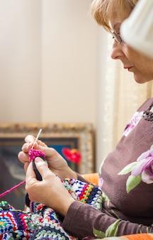 Porträt einer frau, die eine vintage-wolldecke strickt