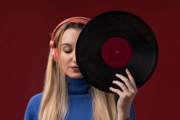 Porträt einer frau, die eine vinylscheibe hält