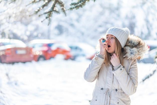 Porträt einer frau, die einen asthma-inhalator in einem kalten winter verwendet