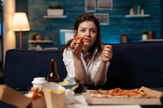 Porträt einer frau, die einen comedy-film sieht und ein leckeres pizzastück isst, das sich auf dem sofa entspannt?