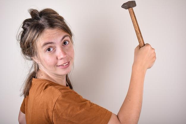 Porträt einer frau, die einen hammer hält