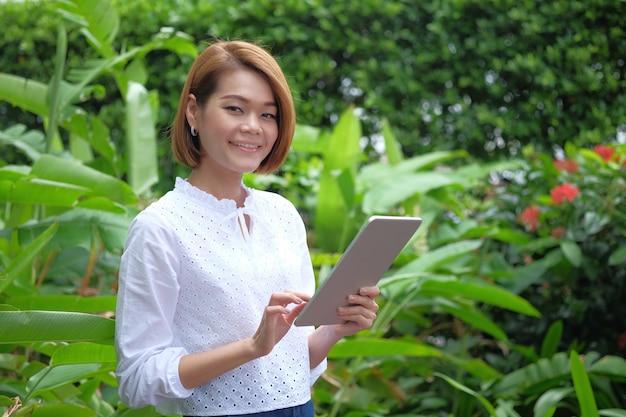 Porträt einer frau, die einen tabletten-pc halten steht. lächelnde frau am grün im freien mit kopienraum