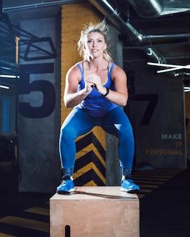 Porträt einer frau, die gedrungene übung auf holzkiste im fitness-club tut