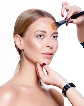 Porträt einer frau, die ihr make-up macht