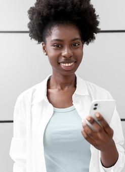 Porträt einer frau, die ihr smartphone hält