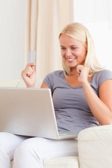 Porträt einer frau, die ihre kreditkarte verwendet, um online zu kaufen