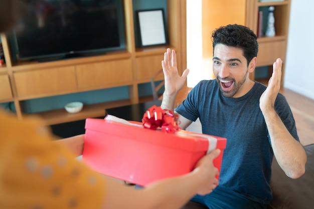 Porträt einer frau, die ihren freund mit einem geschenk überrascht. feier und valentinstag konzept.