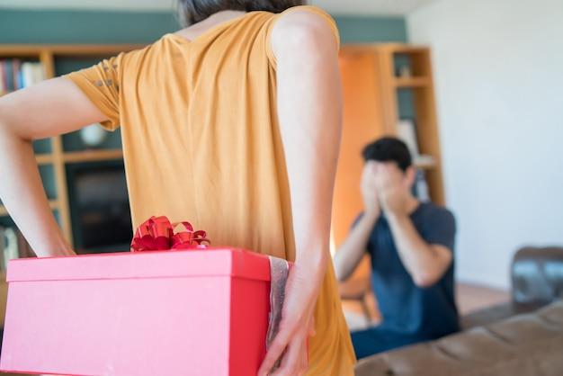 Porträt einer frau, die ihren freund mit einem geschenk überrascht