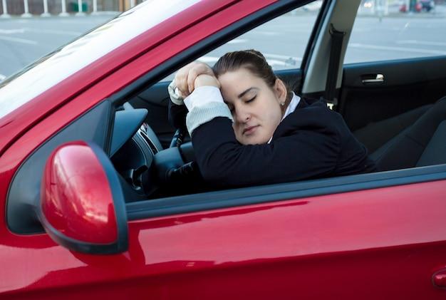 Porträt einer frau, die im auto auf dem fahrersitz schläft