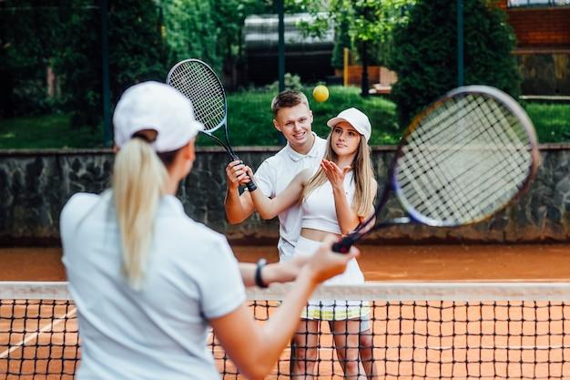Porträt einer frau, die im tennis mit trainer spielt.