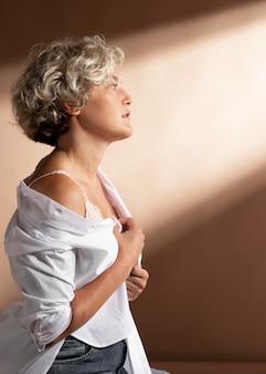 Porträt einer frau, die im weißen hemd posiert und ihren bh zeigt
