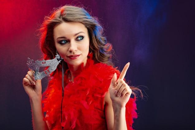 Porträt einer frau, die karnevalsmaske in ihren händen hält