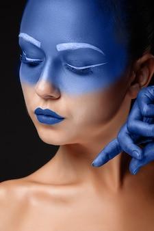 Porträt einer frau, die mit blauer farbe bedeckt ist