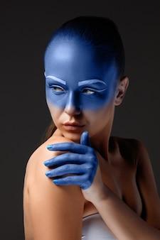 Porträt einer frau, die mit blauer farbe bedeckt posiert