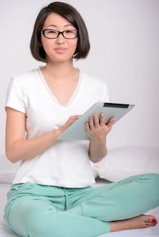 Porträt einer frau, die sich zu hause entspannt und eine tablette verwendet.