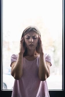 Porträt einer frau, die unter kopfschmerzen leidet