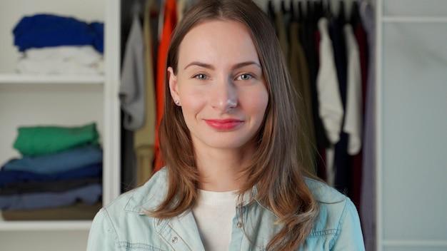 Porträt einer frau, die vor dem hintergrund eines großen kleiderschranks einen kleiderschrank mit stilvollen kleidern und haushaltsgegenständen steht.