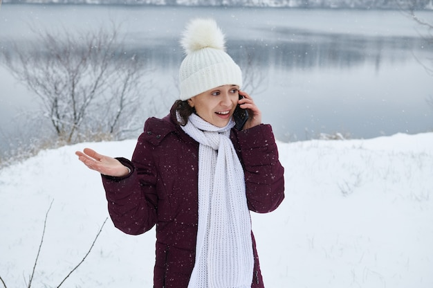 Porträt einer frau, die weiße wollmütze und schal trägt, die auf handy sprechen