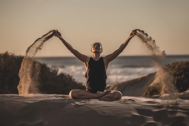 Porträt einer frau, die yoga am strand tut