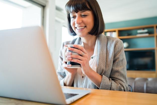 Porträt einer frau, die zu hause arbeitet und einen videoanruf mit laptop führt