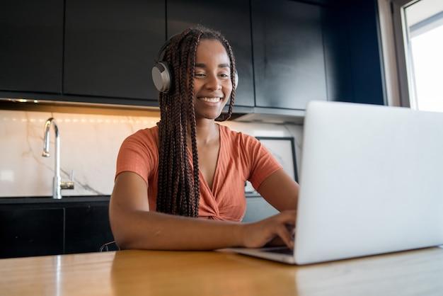 Porträt einer frau, die zu hause arbeitet und einen videoanruf mit laptop hat. home-office-konzept. neuer normaler lebensstil.