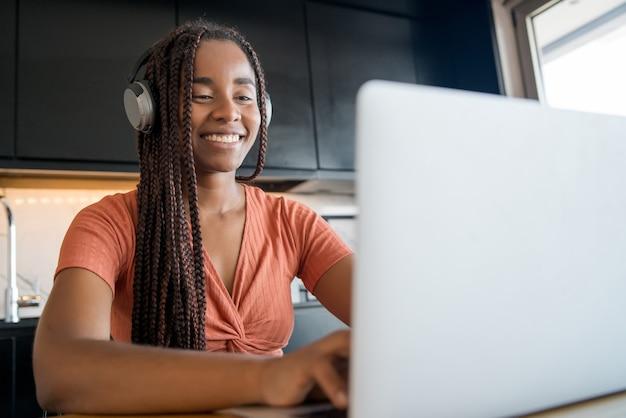 Porträt einer frau, die zu hause arbeitet und einen videoanruf mit laptop hat. home-office-konzept.