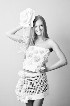 Porträt einer frau im papierkleid mit blume auf grauem hintergrund. schwarz-weiß-fotografie