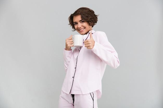 Porträt einer frau im pyjama, die eine teetasse hält