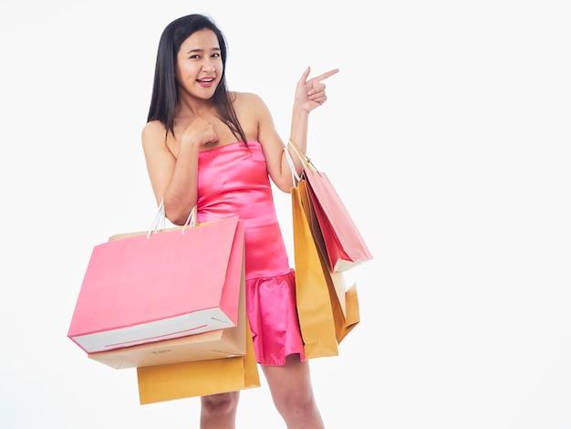 Porträt einer frau im rosa kleid mit einkaufstüten isoliert auf weißem hintergrund
