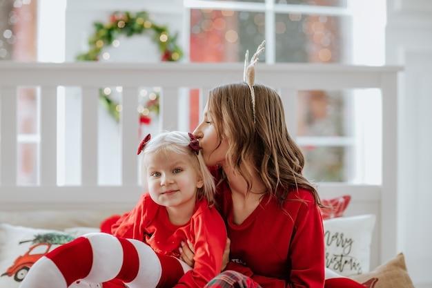 Porträt einer frau im roten winterpyjama und einem stirnband wie die hirschhörner, die ihr mädchen küssen