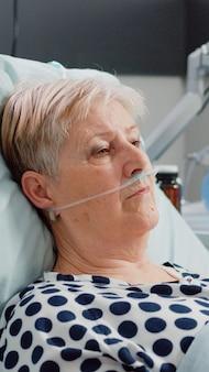 Porträt einer frau im ruhestand mit krankheit im bett liegend