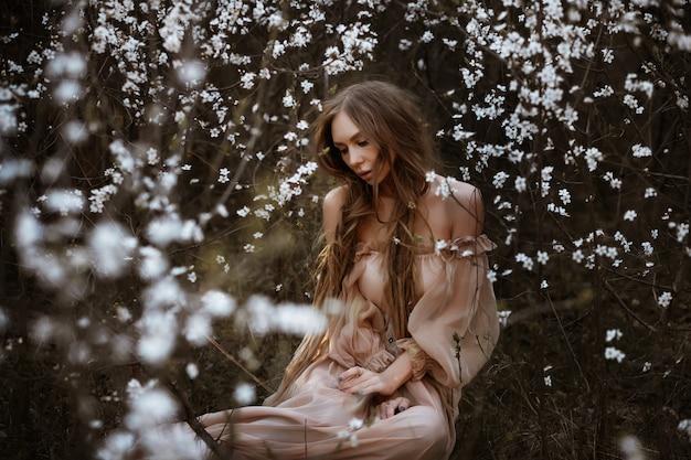 Porträt einer frau in blühenden büschen im garten. frühling