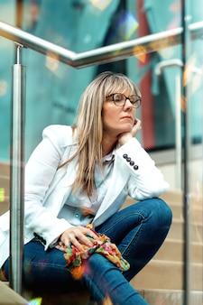 Porträt einer frau in den gläsern, die auf der treppe im stadtzentrum sitzen
