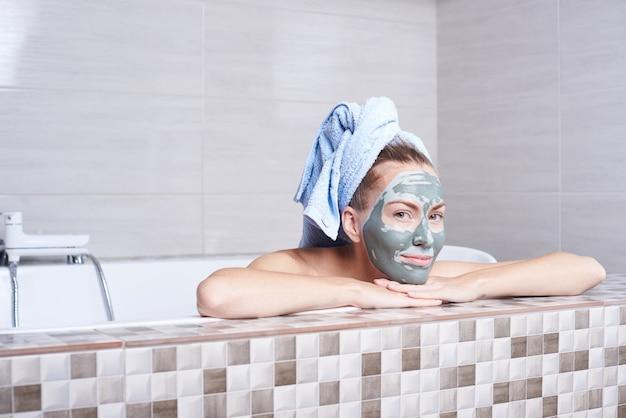 Porträt einer frau in der gesichtsalginatmaske, die im retro-bad im badezimmer liegt