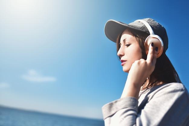 Porträt einer frau in der sonnenbrille, die eine kappe trägt, die musik auf dem hintergrund des meeres genießt.