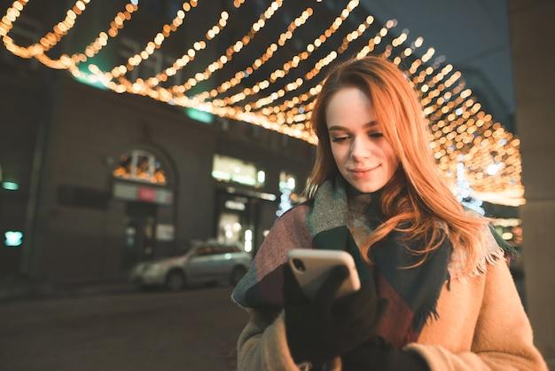 Porträt einer frau in der warmen kleidung, die vor dem hintergrund einer nachtstadt steht und ein smartphone benutzt