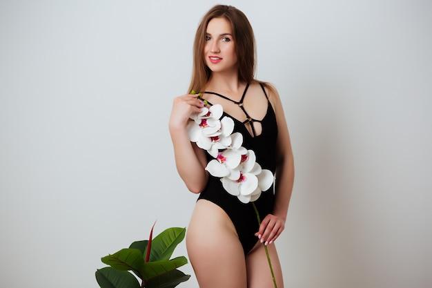 Porträt einer frau in einem badeanzug, der eine orchidee hält. sinnliche sexy frau