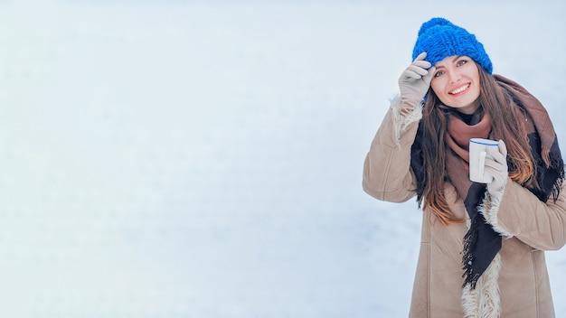 Porträt einer frau in einem blauen hut mit einer tasse auf einem hintergrund des schnees