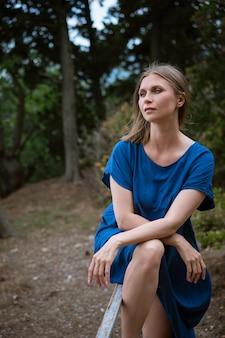 Porträt einer frau in einem blauen kleid auf einem der natur