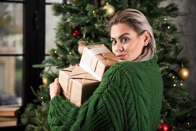 Porträt einer frau in einem grünen pullover, der geschenke hält