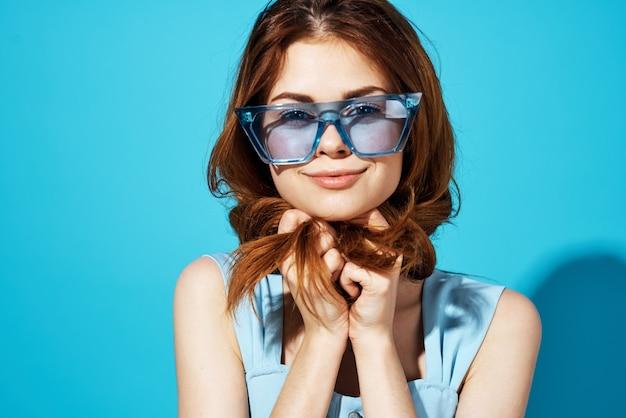 Porträt einer frau in einem kleid und brille blauem hintergrund lifestyle. foto in hoher qualität
