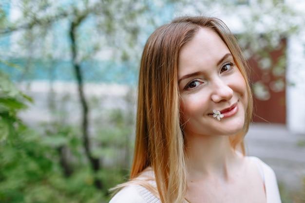 Porträt einer frau in einer weißen bluse, die ein kirschblütenblatt in ihrem mund hält