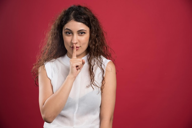 Porträt einer frau in freizeitkleidung, die handgeste zeigt, schweigen auf rot.