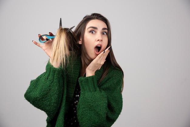 Porträt einer frau in grüner jacke, die ihr haar mit einer schere schneidet.