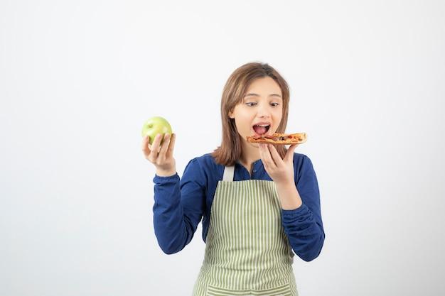 Porträt einer frau in schürze, die pizza wählt, um über gesundem apfel zu essen?